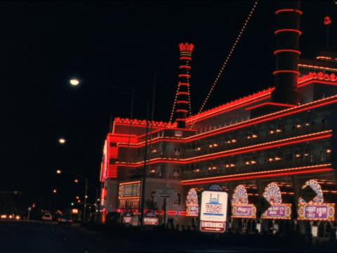 traffic drives past hotels on the las vegas strip. - las vegas hilton stock-videos und b-roll-filmmaterial