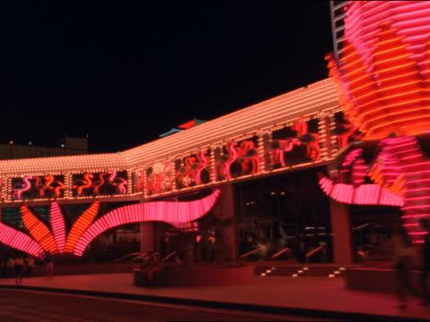 traffic drives past the flamingo hilton in las vegas. - las vegas hilton stock-videos und b-roll-filmmaterial