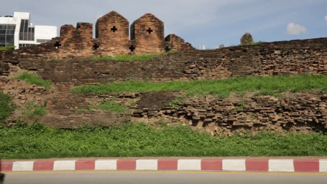 traffic drives past the old city wall of chiang mai thailand on sunday june 19 traffic drives past the moat and the old city wall of chiang mai... - moat stock videos and b-roll footage