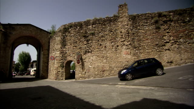 traffic drives through a narrow arch in the town wall of arezzo, italy. available in hd. - 要塞点の映像素材/bロール