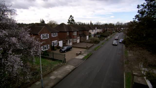 Traffic drives through a suburban neighborhood, Rayners Lane, London. Available in HD.