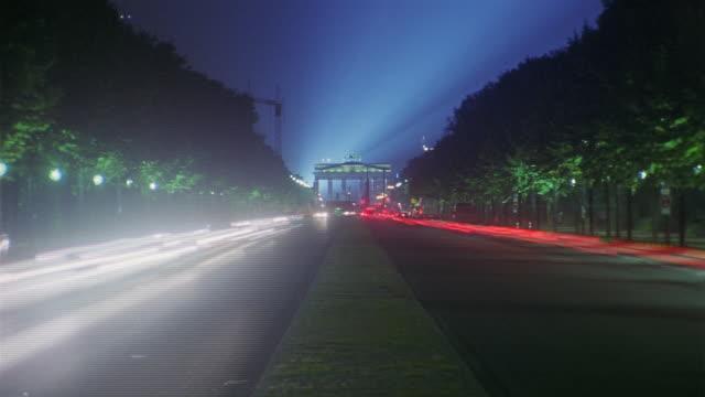 vídeos y material grabado en eventos de stock de traffic drives through berlin's brandenburg gate at night. - luz trasera
