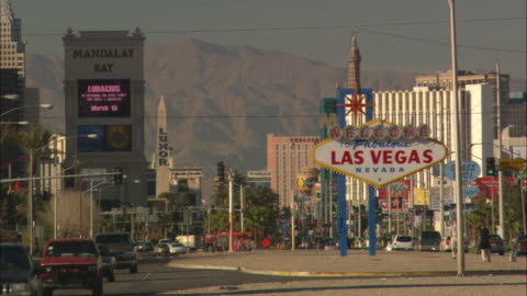 traffic drives through las vegas, nevada. - welcome sign stock videos & royalty-free footage