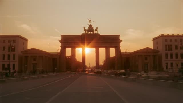 Traffic drives through the Brandenburg Gate in Berlin, Germany.