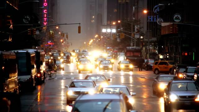 traffic drives up sixth avenue on a rainy evening in new york city. - ペディキャブ点の映像素材/bロール