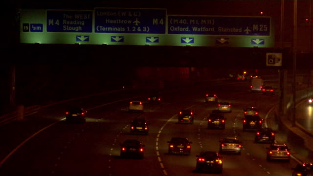 ha ws traffic driving below heathrow airport sign on m25 motorway at night / london, england - heathrow airport stock videos and b-roll footage
