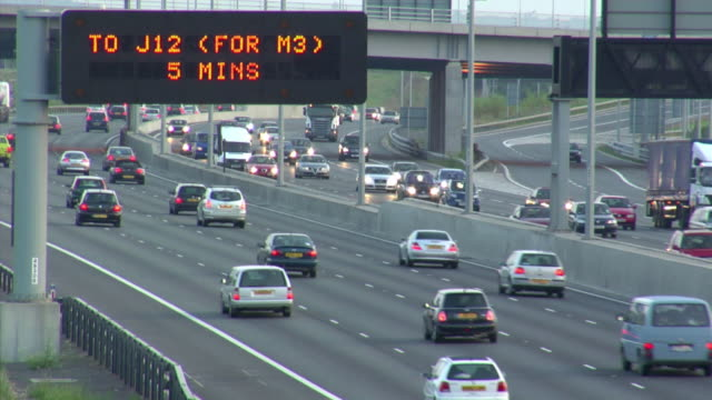 ha ws traffic driving below junction sign on m25 motorway in early evening / london, england - m25 video stock e b–roll