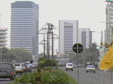 traffic driving on either side of jakarta highway median with buildings in background - median nerve stock videos & royalty-free footage