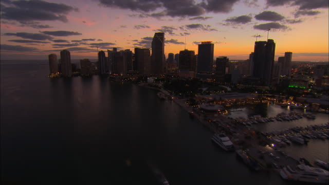 AERIAL WS Traffic driving on MacArthur Causeway past Watson Island with view of sunset skyline / Miami, Florida, USA