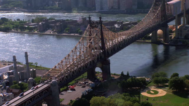 AERIAL Traffic driving on Queensboro Bridge passing over Roosevelt Island, and Manhattan skyline / New York City, New York, United States