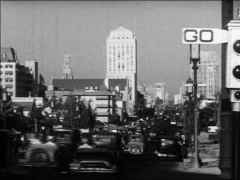vídeos de stock e filmes b-roll de b/w 1930 rear view traffic driving on wide city street / buildings in background / los angeles, ca - 1930