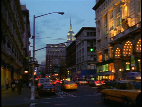 vidéos et rushes de pan traffic driving past 6th avenue + 18th street at dusk / empire state building in background - 1990 1999