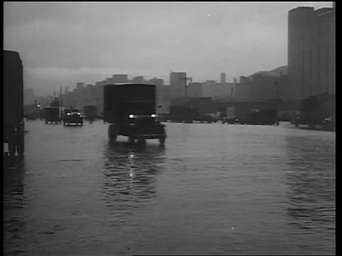 B/W 1933 traffic driving past camera on rainy street / end of Prohibition