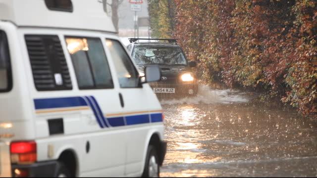 traffic driving through flood water during torrentail rain in ambleside, lake district, cumbria, uk. - van stock videos & royalty-free footage