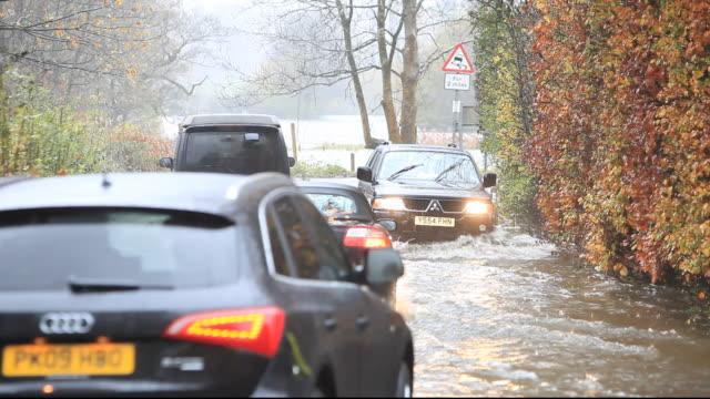 vídeos y material grabado en eventos de stock de traffic driving through flood water during torrentail rain in ambleside, lake district, cumbria, uk. - inundación