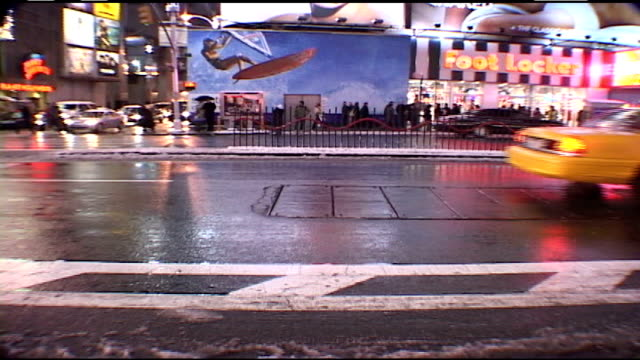 traffic driving through snowy times square at night - stagione video stock e b–roll