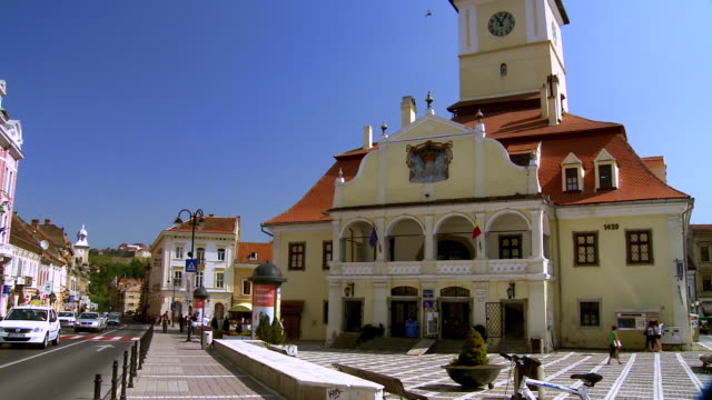 ms td pan traffic flowing in front of century buildings / brasov, romania - トランシルバニア点の映像素材/bロール