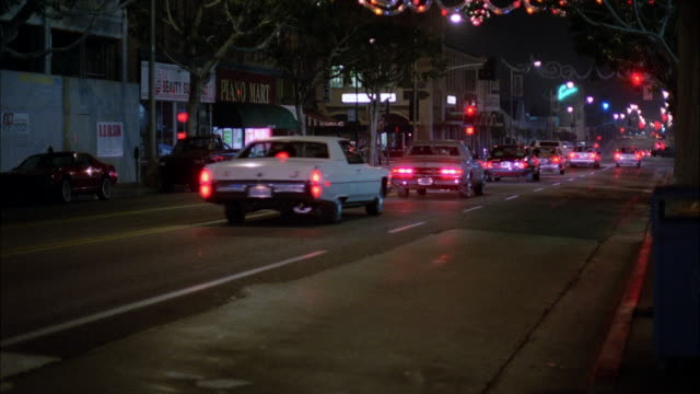 ms pan traffic flowing on busy street at night / hollywood, california, united states - 1987 stock-videos und b-roll-filmmaterial