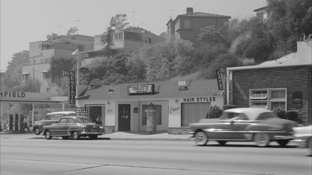 ms traffic flowing on street near shops / hollywood, california, united states - anno 1958 video stock e b–roll