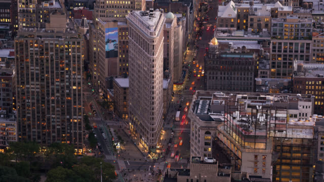 t/l ha traffic flows beside the flatiron building at dusk - flatiron building manhattan stock videos and b-roll footage