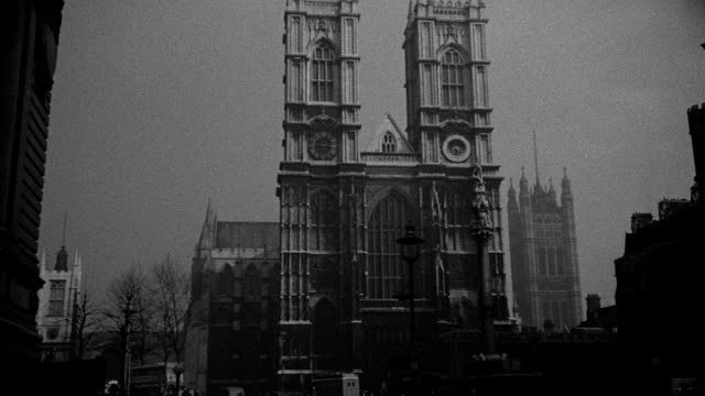 traffic flows on a london street near westminster abbey. - westminster abbey stock videos & royalty-free footage