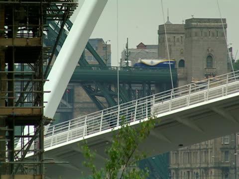 traffic flows on an old iron bridge alongside the gateshead millennium bridge. - tyne and wear stock videos & royalty-free footage