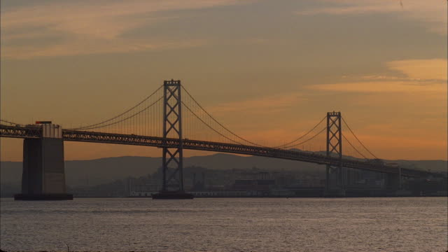 traffic flows over san francisco's golden gate bridge as sunset tints the sky in soft pastels. - san francisco bay stock videos & royalty-free footage