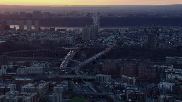 stockvideo's en b-roll-footage met traffic flows over the george washington bridge, across washington heights, and into the bronx at sunset. - george washington