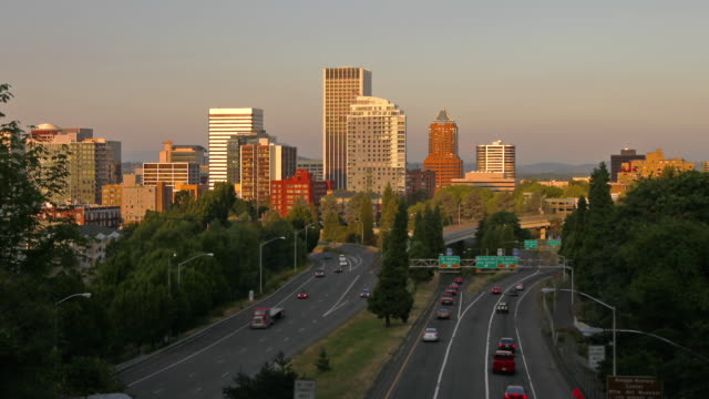 Traffic flows quickly along a highway toward Portland, Oregon at sunset.