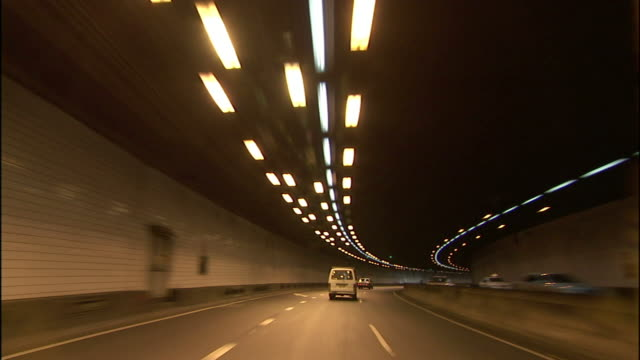 traffic flows through an illuminated tunnel in sydney. - car point of view stock videos & royalty-free footage