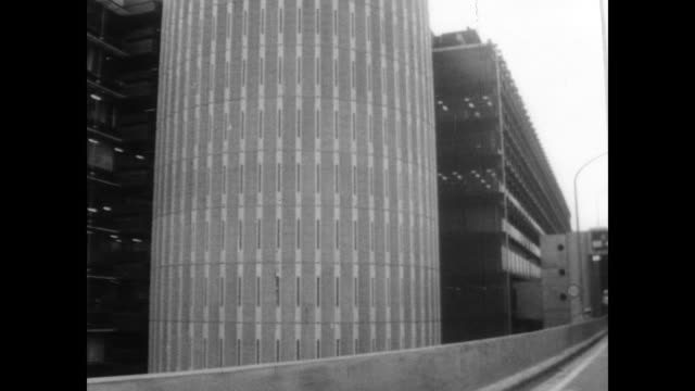 traffic in downtown tokyo / modern office buildings across the street from traditional style houses and bridges / women in traditional costume... - 1967年点の映像素材/bロール