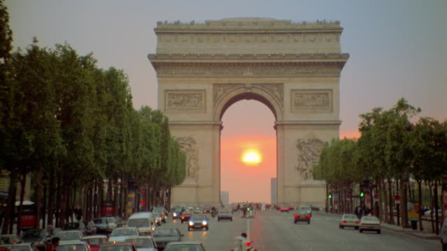 Traffic in front of Arc de Triomphe at sunset / Paris