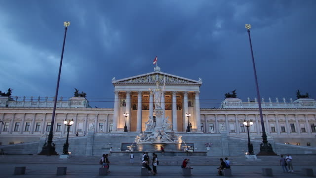 ws traffic in front of austrian parliament building at dusk / vienna, austria - traditionally austrian stock videos & royalty-free footage