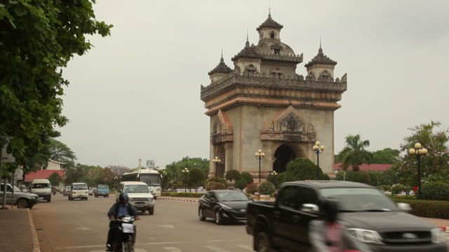 ws traffic in front of patuxai gate in thannon lanxing / vientiane, laos - laos stock videos and b-roll footage