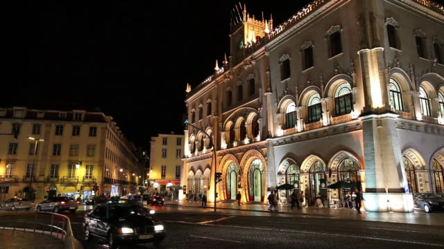 ws traffic in front of rossio railway station illuminated at night / lisbon, portugal - ornate stock videos & royalty-free footage
