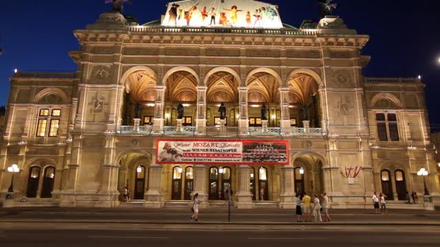 vídeos de stock, filmes e b-roll de ws traffic in front of vienna state opera at night / vienna, austria - teatro de ópera
