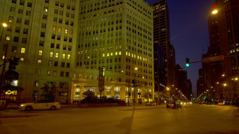 medium pan traffic in front of wrigley building on michigan avenue at night - wrigley building video stock e b–roll