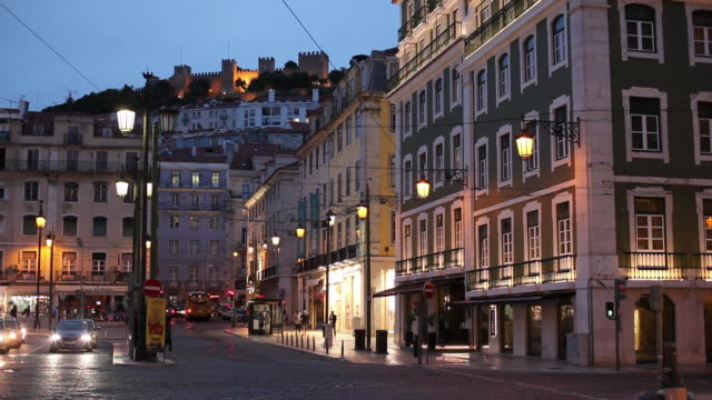 stockvideo's en b-roll-footage met ws traffic in old town and castle of sao jorge at dusk / lisbon, portugal - oude stad