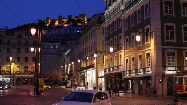 ws traffic in old town and castle of sao jorge at night / lisbon, portugal - campo totale video stock e b–roll