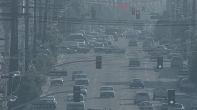 Traffic in smog on unidentified six lane boulevard lined w/ a forest of telephone poles every few feet Flores Street Sweetzer Avenue cross street...