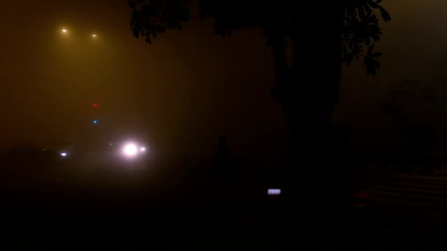 traffic in the city during foggy night time lapse - delhi stock videos & royalty-free footage