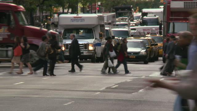 vídeos y material grabado en eventos de stock de traffic is stopped while people cross the street and cross street traffic passes by. - paso de cebra