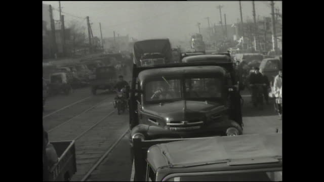 a traffic jam stops vehicles on a busy street. - 1950~1959年点の映像素材/bロール