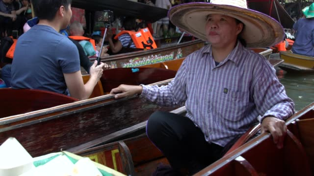traffic jam with boats on a narrow canal the damnoen saduak floating market - floating market stock videos & royalty-free footage