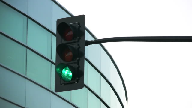 hd: traffic light and office building loop. - green light stoplight stock videos and b-roll footage