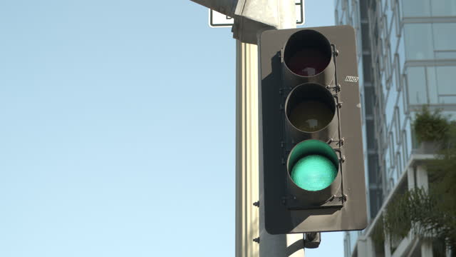 vídeos y material grabado en eventos de stock de a traffic light changes at an intersection, daytime - luz verde semáforo