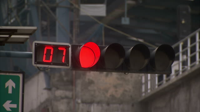 A traffic light glows red as a digital counter counts time left to cross.