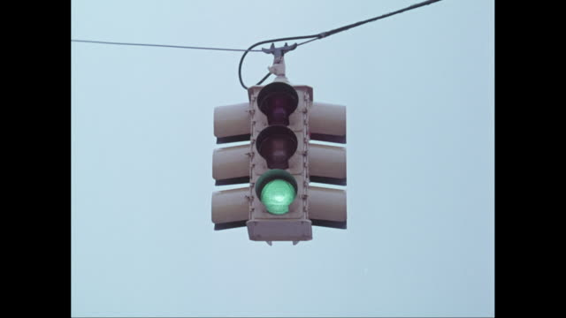 MS Traffic light hanging over street against clear sky / United States