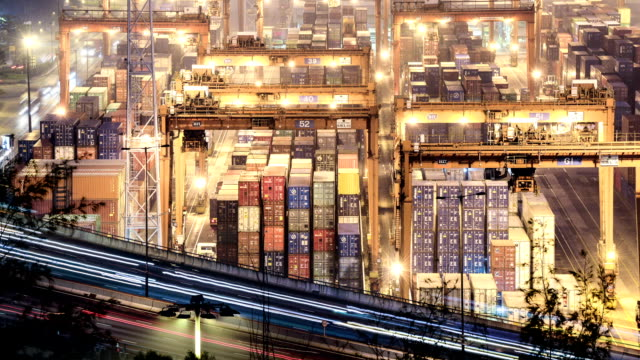 traffic light trails and busy container harbor hong kong at night, timelapse.