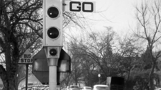 """B/W MS traffic light with """"go"""" sign changing to """"stop"""" on suburban road with traffic"""